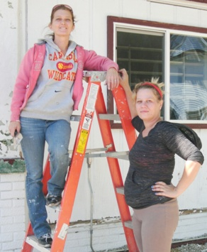 Julie Evans and co-worker cleaning up the exterior of 687 E. Court St for the new owner.